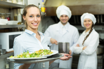 Team of chefs and female waiter at restaurant kitchen